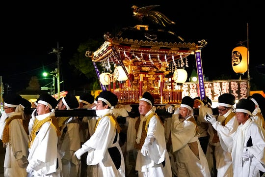 In this Tuesday, Dec. 3, 2019, photo,  white-clad men carry a mikoshi, a portable shrine, during the Chichibu Night Festival in Chichibu, north of Tokyo, Japan. Shinto is Japan's indigenous religion that goes back centuries. It is an animism that believes there are thousands of kami, or spirits, inhabiting nature, such as forests, rivers and mountains.
