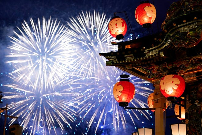 In this Tuesday, Dec. 3, 2019, photo, a lantern-covered float stands as fireworks light up the sky during the Chichibu Night Festival in Chichibu, Japan. Moving six towering floats up a hill and into the town center is the culminating moment of a Shinto festival that has evolved from a harvest thanksgiving into a once-a-year meeting between two local gods.