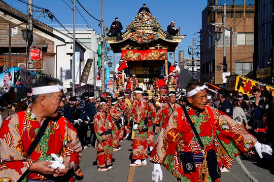 In this Tuesday, Dec. 3, 2019, photo, participants clad in kimonos prepare to pull a float before it goes to the town central square at the Chichibu Night Festival in Chichibu, north of Tokyo, Japan. Moving six towering floats up a hill and into the town center is the culminating moment of a Shinto festival that has evolved from a harvest thanksgiving into a once-a-year meeting between two local gods. (AP Photo/Toru Hanai)