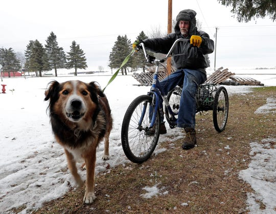Alan Hallisch of Plymouth prepares to go out on his adult tricycle with his dog Coolow, Thursday, December 5, 2019, in Plymouth, Wis. His dog alerted him in February when a fire broke out in his mobile home.