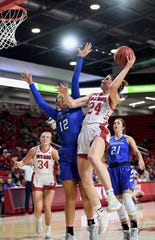 Ciara Duffy of USD jumps up to make a basket as Gracey Griglione of Creighton reaches to block it during their game Wednesday night, Dec. 4, at the Sanford Coyote Sports Center in Vermillion.
