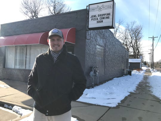 Sunny's Pizzaria owner Jon Oppold stand for a portrait outside his business, set to open Dec. 16.