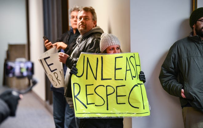 Protesters hold signs outside the office of St. Cloud State University President Robbyn Wacker Thursday, Dec. 5, 2019, in St. Cloud. Layoffs of eight faculty members are planned at the end of this school year.