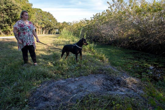 """Audrey Tucker, of western Martin County, and her Rottweiler-mix, Hendrix, revisit the canal they crashed into earlier this week on Southwest Farm Road on Thursday, Dec. 5, 2019, near Indiantown. Tucker was driving her fiancé's car, a 2009 Mitsubishi Eclipse, Tuesday evening when a hog crossed the road. Tucker swerved to miss the animal and crashed into the canal, where Martin County Sheriff's Office Sgt. Anthony Blachowski, assisted by Martin County Fire Rescue EMT Dan McCarthy, pulled her out before rescuing Hendrix. """"I love him so much, he's like my child,"""" Tucker said of Hendrix. """"I wanted to be like, 'forget me, get the dog.'"""""""