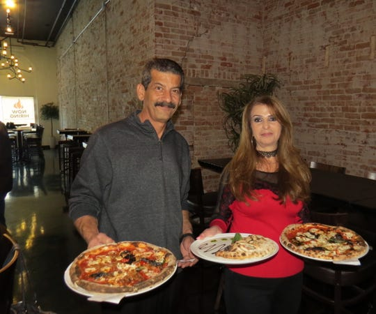 Mike Alshamy and Nadia Alshamy, the husband-and-wife franchisee owners of MidiCi Wood Fired Pizza in Ventura, deliver pizzas and a calzone, center, during the restaurant's pre-opening event for friends and family.