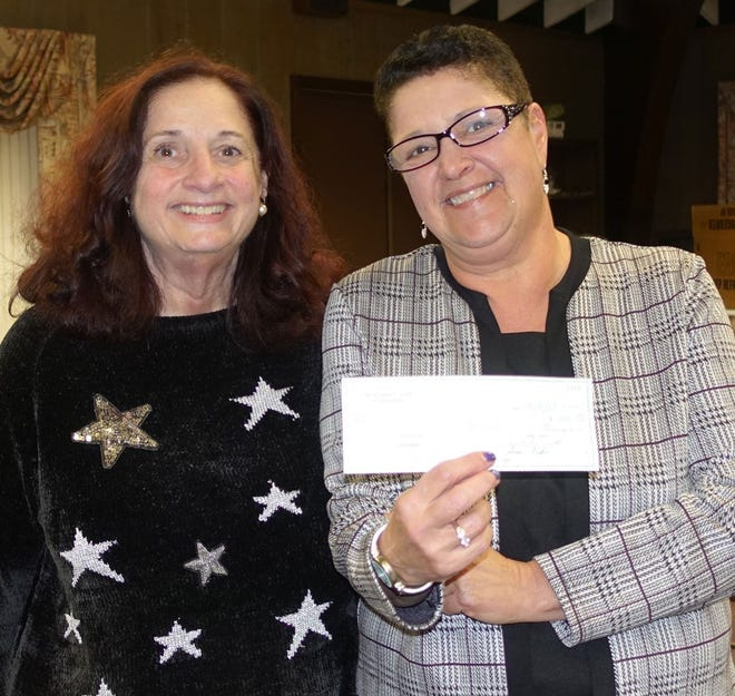 Eva Prestopino (left), president, Woman's Club of Vineland, presents a check for $390 to Mary Ann Hamidy from the Youth Advocacy Program to help sponsor YAP's Christmas/Holiday Party.