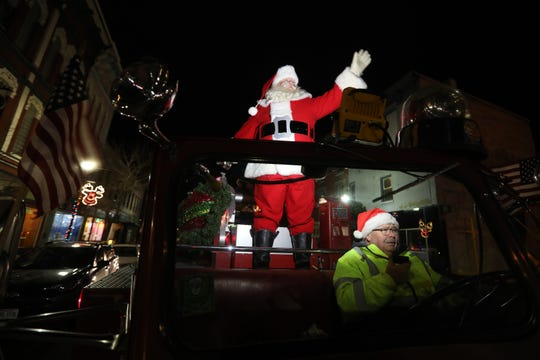 Bo Keck drives Santa down Main Street in Zanesville in the Keck brothers' 1958 Maxim Aerial fire truck during the 26th annual Miracle on Main Street on Wednesday.
