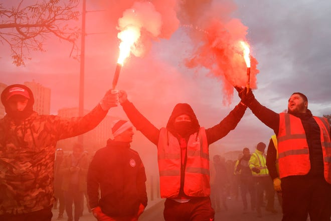 Dockers march with smoke bombs as they take part in a demonstration to protest against the pension overhauls, in Marseille, southern France, on December 5, 2019 as part of a national general strike.