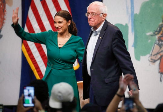 Rep. Alexandria Ocasio-Cortez, D-N.Y stands alongside Democratic presidential candidate Sen. Bernie Sanders, I-Vt., during a campaign rally on Saturday, Nov. 9, 2019, at Drake University in Des Moines, Iowa.  (Bryon Houlgrave /The Des Moines Register via AP) ORG XMIT: IADES109