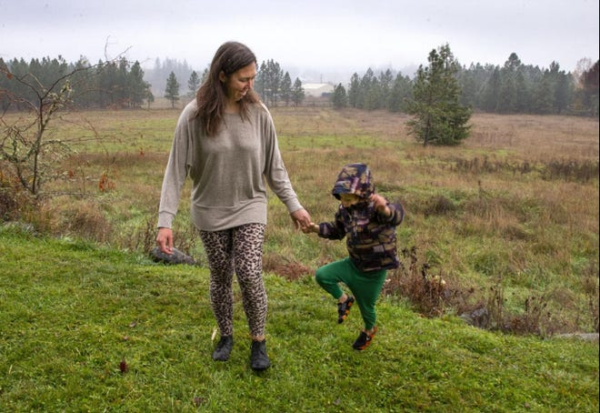 Keelia Carver and her 3-year-old son, Eliot, play in the yard of Carver's parents on a rainy day.
