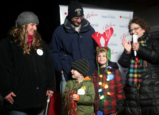 Six-year-old Benjamin Thompson, a boy with acute lymphoblastic leukemia, along with his mother Nicole, father Randy, brother Collin, center, and Patti Gorsky, President and CEO of Make-A-Wish Wisconsin, gets his wish from the Make-A-Wish foundation during a synchronized Christmas light show at his home on Wednesday December 4, 2019, in Appleton, Wis.