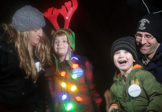 Six-year-old Benjamin Thompson, center left, a boy with acute lymphoblastic leukemia, watches a synchronized Christmas light show with his mother Nicole, brother Collin and his father Randy at his home on Wednesday December 4, 2019, in Appleton, Wis. The light show was a wish granted by the Make-A-Wish foundation and Macy's Believe.