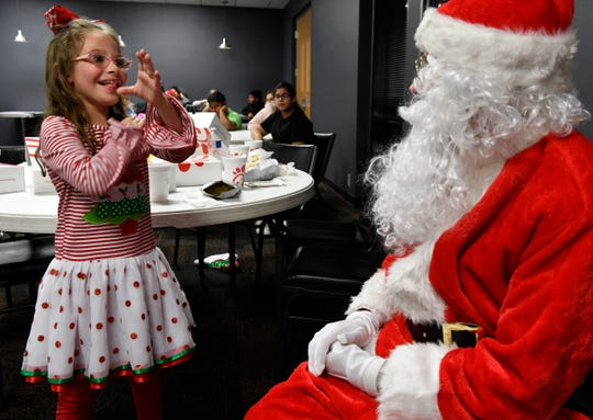 Mia Sanchez, 7, tells Santa Claus what she wants through sign language.