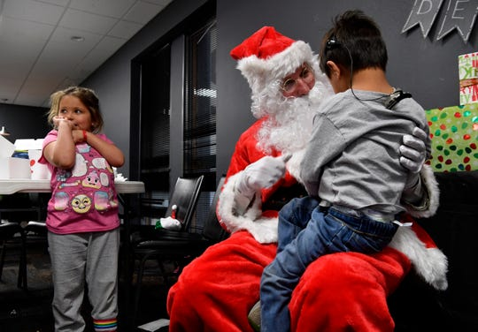 Rosalie Ramirez, 6, waits her turn as Ezekiel Morales, 5, signs with Santa Claus during a Christmas party for deaf students at First Baptist Church's Family Life Center on Thursday.