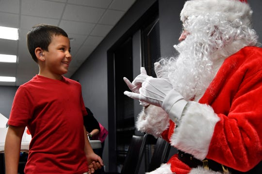 Caleb Devereaux, 6, watches as Santa Claus signs during a Christmas party for deaf students Thursday at First Baptist Church's Family Life Center.