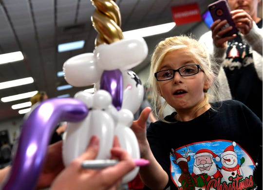 Gracie Casady, 8, reacts as balloon artist Tiffany Martinez hands Gracie her newly-created unicorn.