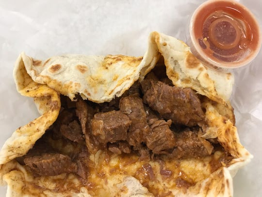 A carne guisada burrito from La Popular Bakery No. 1 at Sayles Boulevard and South First Street features cubed beef stewed in a flavorful, slightly spicy gravy.