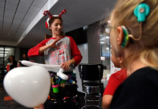 Tiffany Martinez, left, signs with deaf students while making balloon art during Thursday's Christmas party for deaf students at First Baptist Church's Family Life Center. Martinez is an employee with the Abilene Independent School District and works with the Deaf Education program at Ward Elementary School.