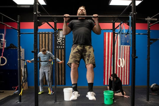 Battle Creek CrossFit owner Clay Moore does pullups on Friday, Dec. 6, 2019 in Battle Creek, Mich. Battle Creek CrossFit recently moved locations from Columbia Ave. to downtown on Michigan Ave.