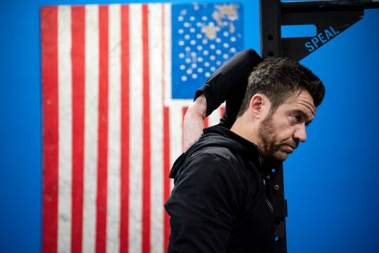 Mick Brutsche stretches at Battle Creek CrossFit on Friday, Dec. 6, 2019 in Battle Creek, Mich. Battle Creek CrossFit recently moved locations from Columbia Ave. to downtown on Michigan Ave.