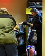 Carol Rose checks out some of the books available at the Friends of the Bucyrus Public Library holiday book sale on Friday afternoon. The sale continues 11 a.m. to 1 p.m. Saturday.
