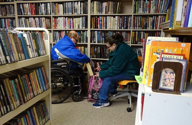 Michael and Jean Wolf bag up their selections at the Friends of the Bucyrus Public Library holiday book sale on Friday afternoon. The sale continues 11 a.m. to 1 p.m. Saturday.