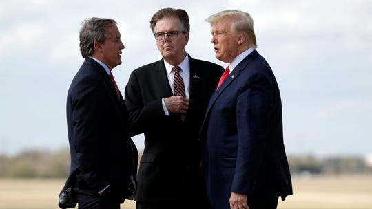 Texas Lt. Gov. Dan Patrick, center, and Attorney General Ken Paxton, greet President Donald Trump at Austin-Bergstrom International Airport, Nov. 20, 2019, in Austin.