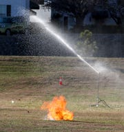 An ignited pumpkin impacts the ground and bursts into more flame on the lawn at Winnfield Dunn Center in Clarksville, Tenn., on Thursday, Dec. 5, 2019.