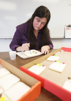 Katie Hultz decorates a cookie during a mentoring program at Coshocton High School recently. Hutlz operates Katie Bakes, specializing in cakes, cupcakes and cookies.