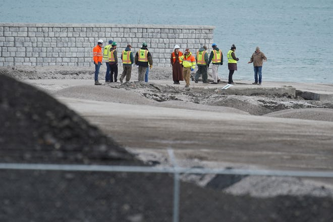 People survey the scene of a Detroit property contaminated with uranium and other dangerous chemicals that partially collapsed into the Detroit River on Friday, Dec. 6, 2019.