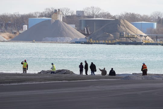 People survey the scene of a Detroit property contaminated with uranium and other dangerous chemicals that partially collapsed into the Detroit River on Friday, December 6, 2019.