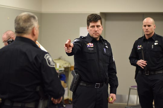 Farmington police Officer Mark Mostek, left, shows how to disarm a person with a gun, as portrayed by Sgt. Michael Flatt during an ALICE training program at the Maxfield Education Center in Farmington.