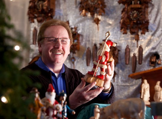 Gerhard Lippman displays one of his hand-carved figures.
