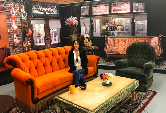 "This Sept. 5, 2019 file photo shows actress Maggie Wheeler, who played Janice on the NBC sitcom ""Friends,"" posing in a replica of the Central Perk set, at the New York City Pop-Up experience in New York."