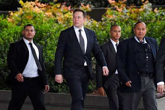 Tesla CEO Elon Musk, second from left, arrives at U.S. District Court Wednesday, Dec. 4, 2019, in Los Angeles. Musk is going on trial for his troublesome tweets in a case pitting the billionaire against a British diver he allegedly dubbed a pedophile.