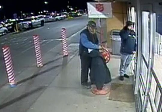 An unidentified man drapes his coat over a Salvation Army donation kettle outside a story in Roseville, then rides off with it on his bicycle.