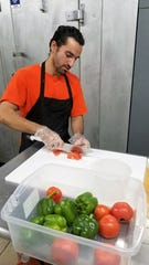 Mohammad Aburumman slices vegetables for sandwiches at Journey Fish and Chicken.
