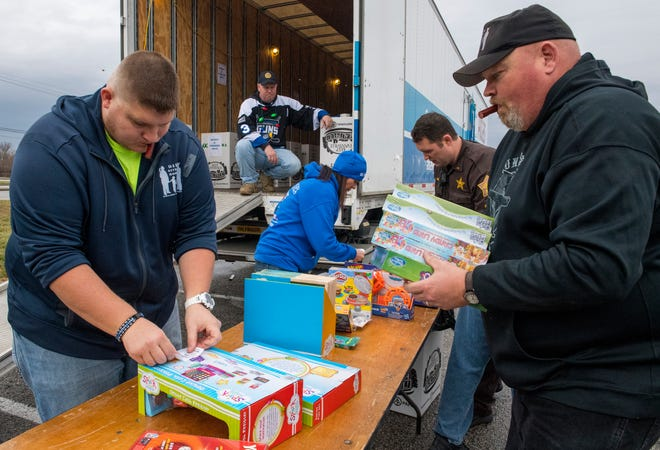 Volunteers sort through and place stickers on donated toys during the 11th annual 911 Gives Hope for the Holidays Toy Drive at the east side Walmart parking lot on Burkhardt Road in Evansville, Ind., Friday morning, Dec. 06, 2019.