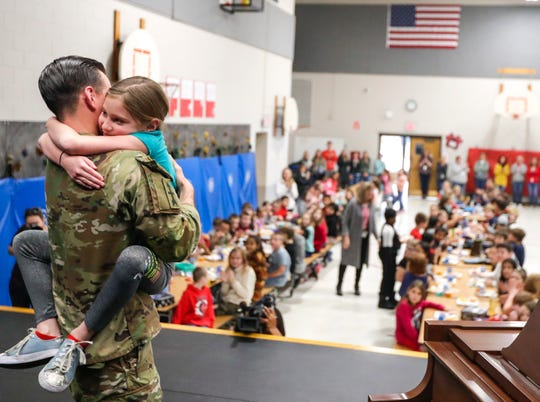 """Isabella hugs her father, 1st Lt.  Anthony Pinchuk of the Wisconsin Army National Guard, after he surprised her as she played """"Jingle Bells"""" to her classmates at lunch on Friday, Dec. 6, 2019, at Webster Elementary School in Allouez, Wis. Pinchuk has been deployed for more than a year in Afghanistan."""