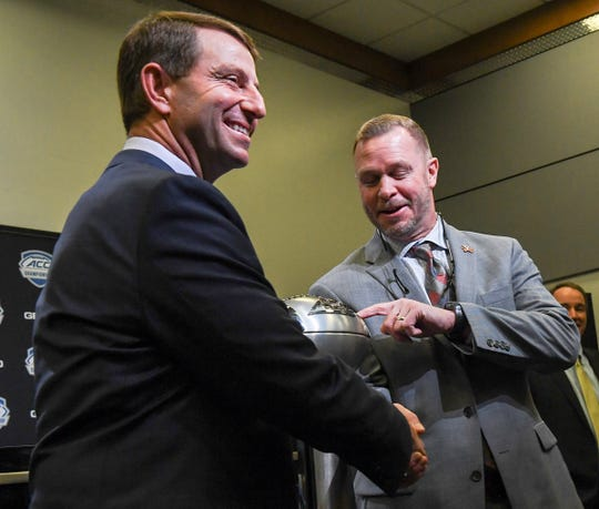 Clemson Head Coach Dabo Swinney and Virginia Head Coach Bronco Mendenhall shake hands with the championship trophy during the ACC football championship pregame press conference at Bank of America Stadium in Charlotte, North Carolina Friday, December 6, 2019.