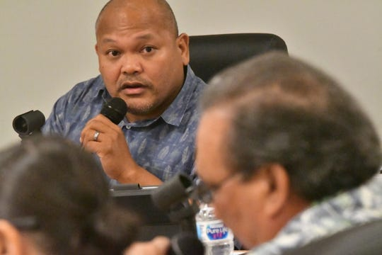 Guam Education Board Chairman Mark Mendiola, with microphone, responds to a question by fellow board member Jon Burch Dec. 6 at Tiyan.
