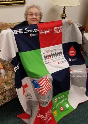 Longtime Red Cross volunteer Ruth Bunch of Henderson shows off a quilt given to mark her service.