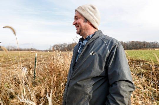 Greg Gunthorp watches his pigs roam around a pasture in LaGrange, Ind., Tuesday, Dec. 3, 2019.