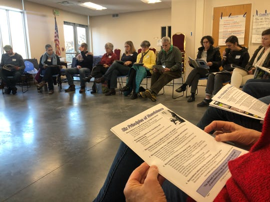 Attendees at a nonviolent response training session read from a manual at the St. Thomas More Catholic Church Dec. 6, 2019, in Coralville.