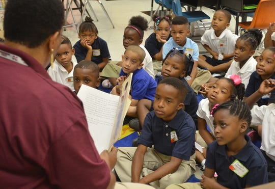 In this 2013 photo, first grade teacher Sheila Gibson reads to her students at Barr Elementary School.