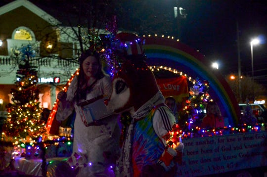 """Richard Patrick, dressed as """"Music City Rudolf,"""" walks next to a woman on stilts as she hands out candy to children from the """"Love is Love"""" float on Thursday."""