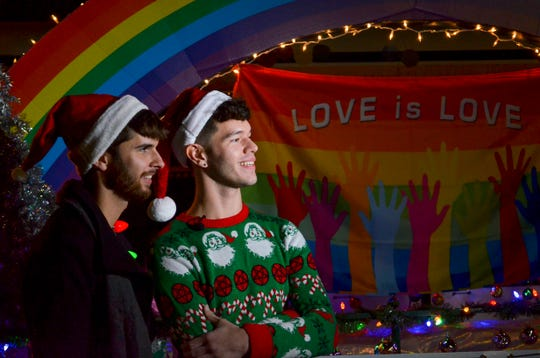"""Travis Long and partner Mathew Tittle smile during an interview in front of the """"Love is Love"""" float before the start of the Union City Christmas Parade on Thursday."""