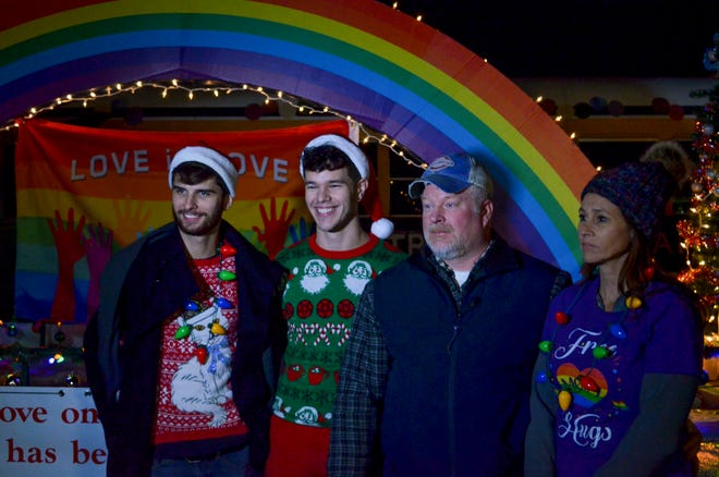 """Dwight Tittle, center right, stands with his wife Robbie Tittle, right, his son Mathew Tittle, center left and Mathew's partner Travis Long in front of their """"Love is Love"""" float before the Union City, Tenn. Christmas Parade on Thursday."""