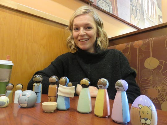 Hannah Kline shows some of the Nativity scene wooden characters she painted to make Jesus and the others look more like people from around the world.