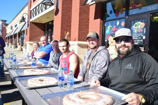 Competitors prepare for the doughnut eating contest at Beaver's Dough Joe one-year anniversary celebration Sunday, Dec. 1. Many were shocked at the size of the doughnut. From left are Kim Ary, Ed Demik, Rich VanKirk, Connor Morel, Timothy Moran and Matt Cohen.